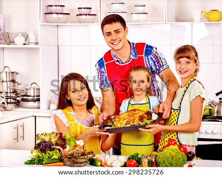 Happy family with father and mother at kitchen. Cooking chicken.