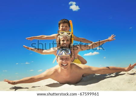 Happy family with flippers lying on sand and looking at camera