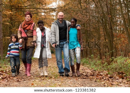 Happy family with foster children in the forest - stock photo