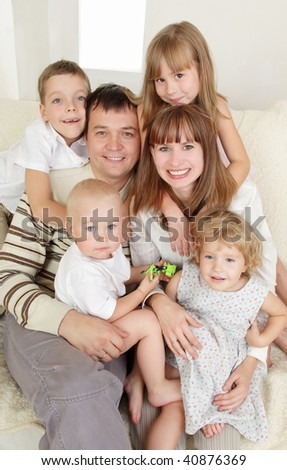 Happy family with four children on sofa