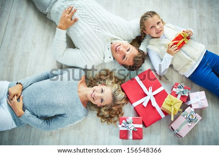 Happy family with giftboxes lying on the floor and looking at camera