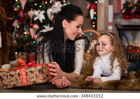Happy family with  gifts lying near Christmas tree at home. Merry Christmas and New Year. - stock photo