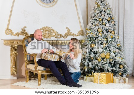 Happy family with  gifts sitting near Christmas tree at home. Merry Christmas and Happy New Year. - stock photo
