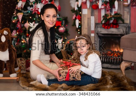 Happy family with  gifts sitting near Christmas tree at home. Merry Christmas and New Year. - stock photo