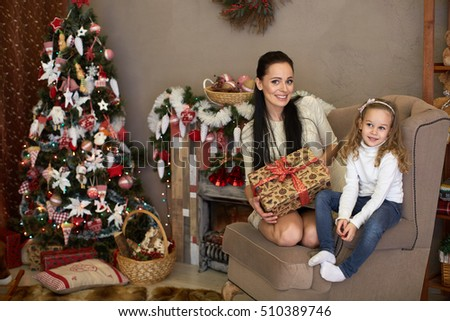 Happy family with  gifts sitting near Christmas tree at home. Merry Christmas and New Year.