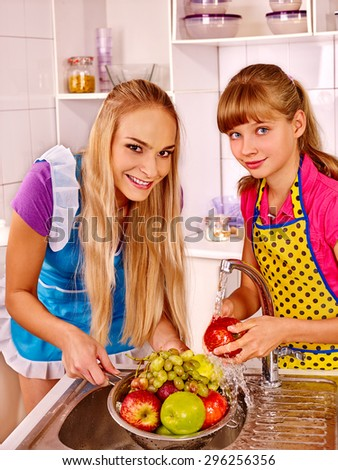 Happy family with girl kid  washing fruit at kitchen. - stock photo