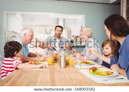 Happy family with grandparents sitting at dining table in home