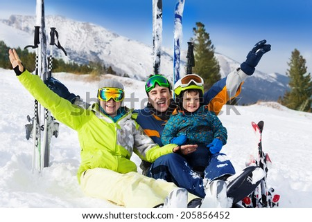 Happy family with hands up sitting on the snow after skiing with ski standing behind