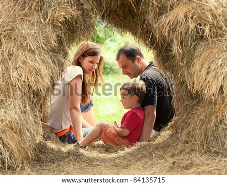 Happy Family with kid  in haystack - stock photo