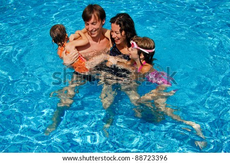 Happy family with kids in swimming pool. Smiling parents and children on summer vacation - stock photo