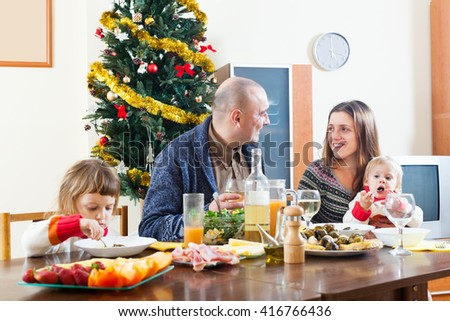 Happy family with kids over celebratory table at home interior