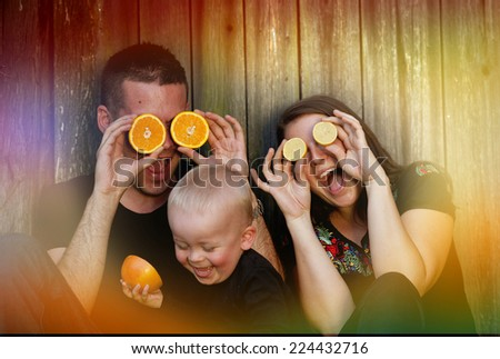 Happy family with little boy sitting by the wooden fence and having fun with oranges - stock photo