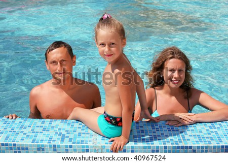 Happy family with little girl bathe in pool, daughter sits near pool - stock photo