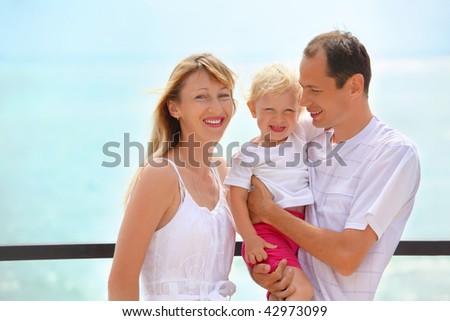 Happy family with little girl on veranda near seacoast - stock photo