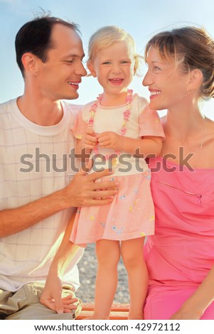 Happy family with little on beach - stock photo