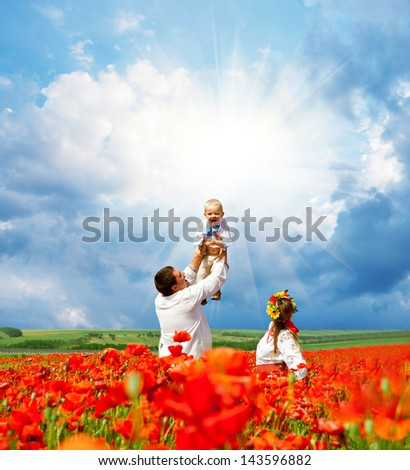 Happy family with little son in traditional ukrainian dress on the poppies field - stock photo