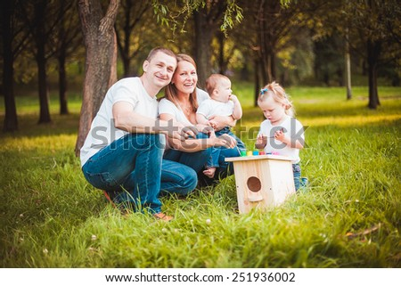 Happy family with nesting box and colorful paints in green summer forest - stock photo