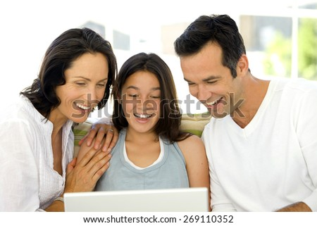 Happy Family with one child using laptop - stock photo