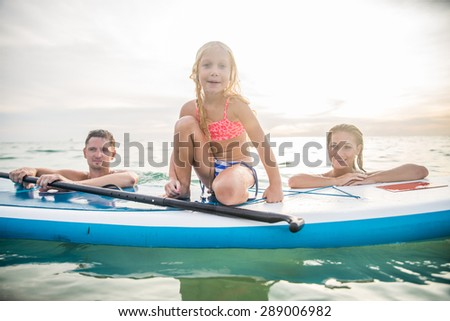 Happy family with paddle board swimming in the ocean - Pretty young girl smiling while learning to paddle - Portrait of active and sportive family on vacation on summertime - stock photo