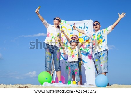 Happy family with paint  playing on the beach at the day time. Concept of friendly family.