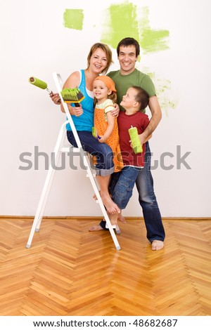 Happy family with painting utensils before redecorating their home - stock photo