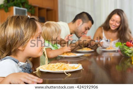 Happy family with playful kids eating with spaghetti at table. Focus on girl