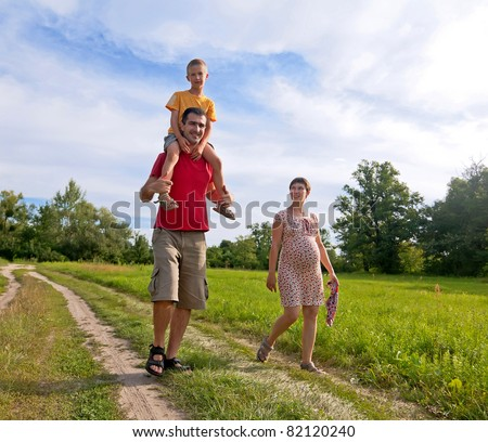 Happy family with pregnant woman, kid and father walking on the road  - stock photo