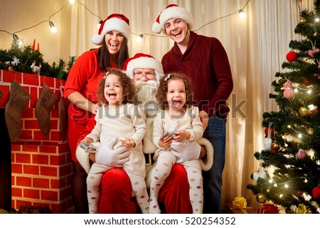 happy family with santa claus laughing and smiling mother father daughter twin girls - Pictures With Santa Claus