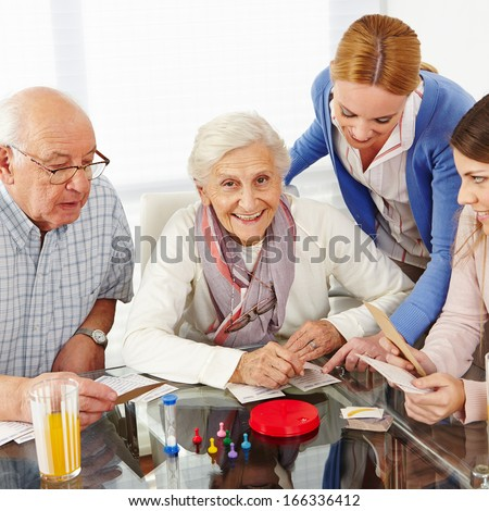 Happy family with senior couple playing parlor games - stock photo