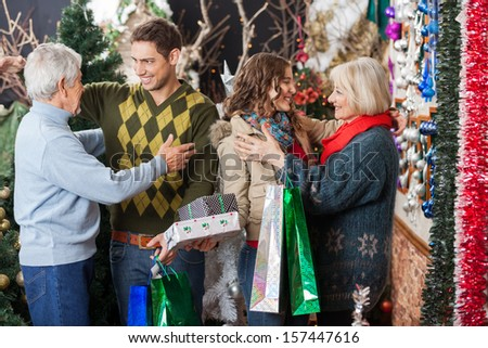 Happy family with shopping bags and presents embracing each other in Christmas store - stock photo