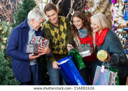 Happy family with shopping bags and presents in Christmas store - stock photo