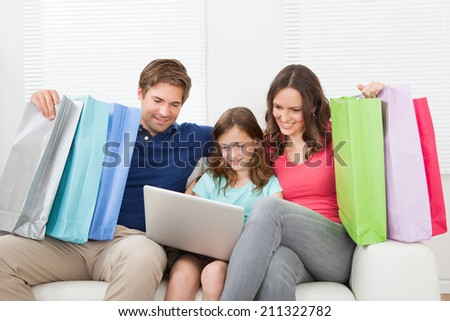 Happy family with shopping bags using laptop while relaxing on sofa at home - stock photo