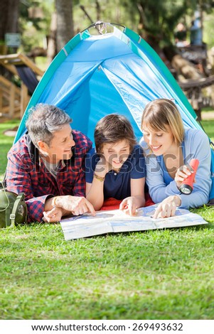 Happy family with son reading map in tent at park - stock photo