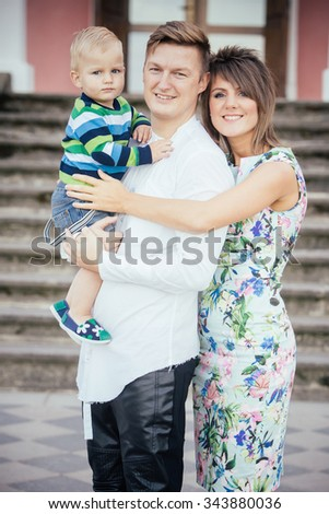 Happy family with son standing outdoors in Summer. - stock photo