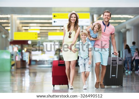 Happy family with suitcases in the airport - stock photo