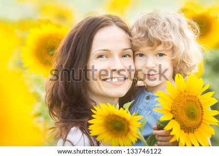 Happy family with sunflowers having fun outdoors in spring field - stock photo