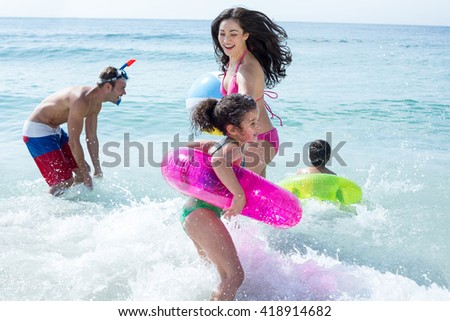 Happy family with swimming ring playing in sea - stock photo