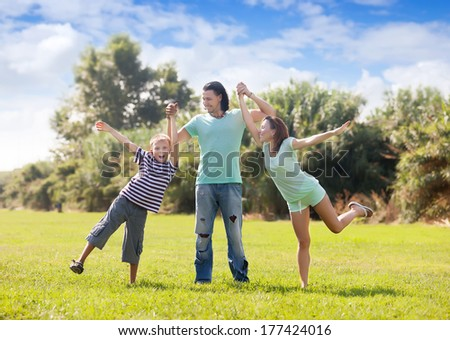 Happy family  with teenage boy enjoying time in summer park