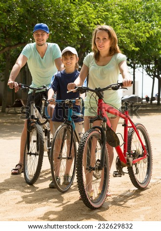 Happy family with teenager son staying with bicycles in the street in summer day  - stock photo