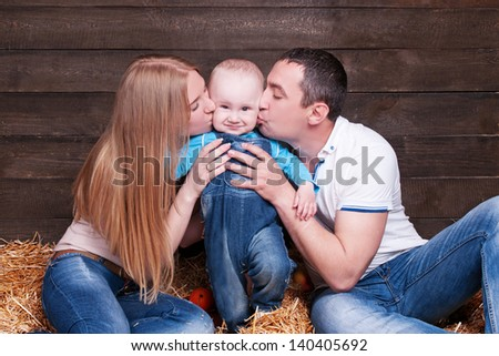 Happy family with the child - beautiful mother and father hug their son, posing on hay in studio closeup - stock photo