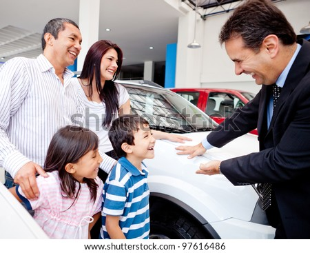 Happy family with the dealer buying a new car - stock photo