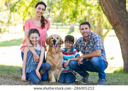 Happy family with their dog in the park on a sunny day - stock photo