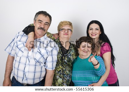 Happy family with  three generations of women grandmother,mother ,daughter and father  posing in a big embrace ,elderly woman pointing to you - stock photo