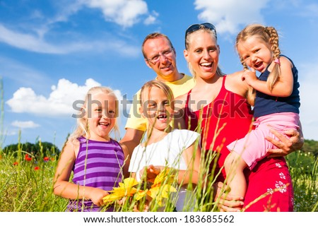 Happy family with tree kids standing in a field of wild flowers together  - stock photo