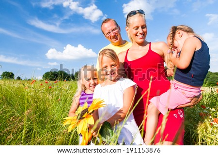 Happy family with tree kids standing in a field of wild flowers together
