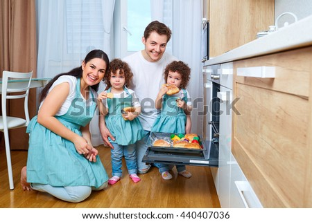 Happy family with twin daughters in the kitchen. Cheerful mother, father, two daughters, twin preparing food in the kitchen. The concept of a happy family. - stock photo