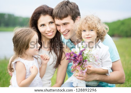 Happy family with two children and bouquet of spring flowers having fun outdoors. Farmland vacations concept - stock photo