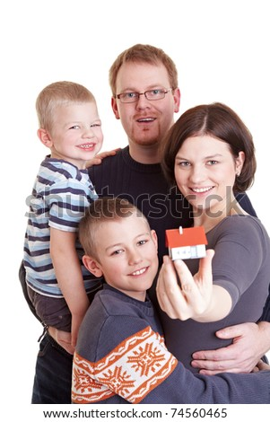 Happy family with two children holding miniature home - stock photo