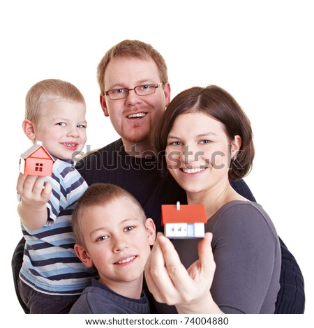 Happy family with two children holding small houses - stock photo