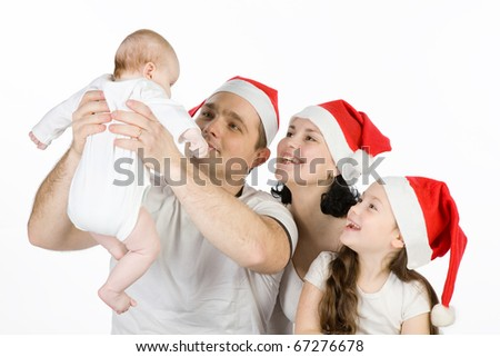 Happy family with two children in Christmas red caps. - stock photo